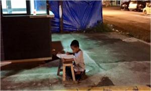 Мальчик делает уроки при свете от «Макдоналдса»