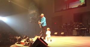 Малыш выбегает на сцену, чтобы обнять папу. То, что он делает на 0:27, заставляет публику визжать!